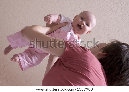 mother swings baby into the air - stock photo