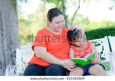 mother takes care her daughter with gentle love and the child is reading a book - stock photo