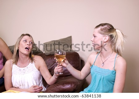 Mother Taking a Drink Away from Her Teenage Daughter - stock photo
