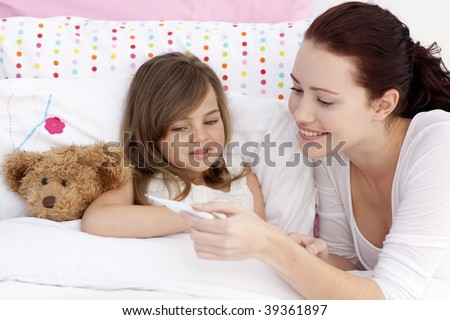 Mother taking her daughter's temperature in bed - stock photo