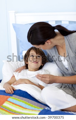 Mother taking her son's temperature with a thermometer lying in bed - stock photo