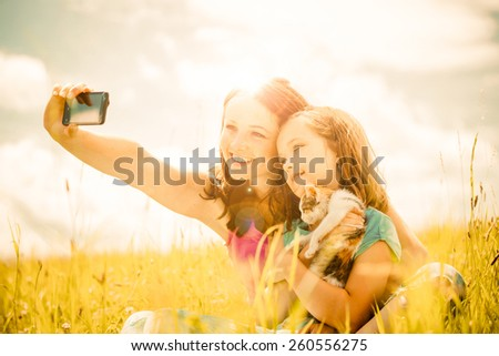 Mother taking photo with her smart-phone camera of herself, her girl and kitten - outdoor in nature - photo with lens flare - stock photo