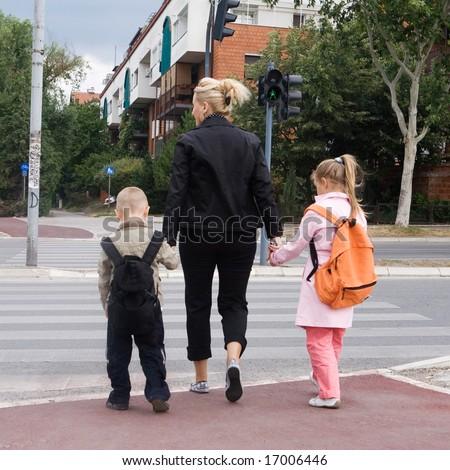 mother taking the children across the street - stock photo