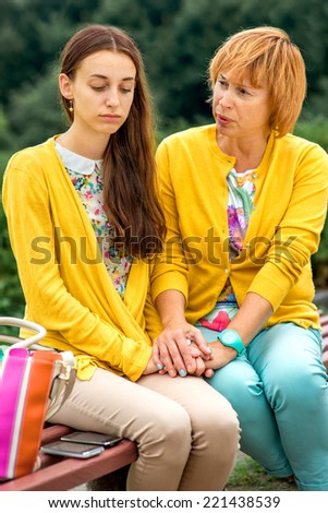 Mother talking to her daughter sitting on the bench in the park