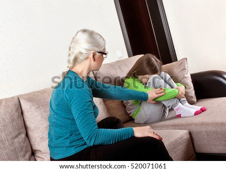 Mother talking with daughter sitting on sofa at home