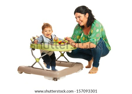 Mother talking with her baby son in walker against white background