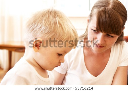 mother talking with her unhappy son at home - stock photo