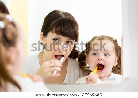 mother teaches child brushing teeth - stock photo