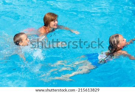Mother teaches children to swim in the summer outdoor pool.