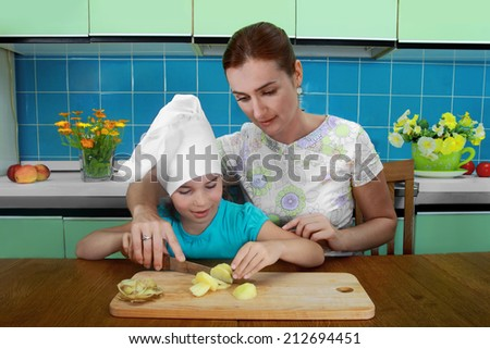 Mother teaches daughter to cut the potatoes in the kitchen - stock photo