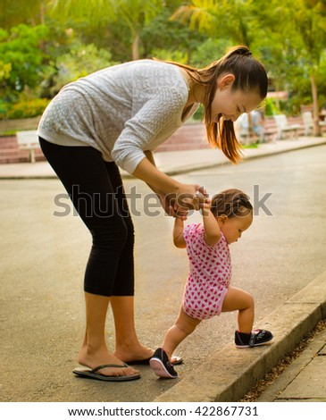 Mother teaches her baby daughter how to walk on a nice afternoon - stock photo