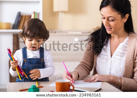 Mother teaches her baby girl to draw.They sitting in living room. - stock photo