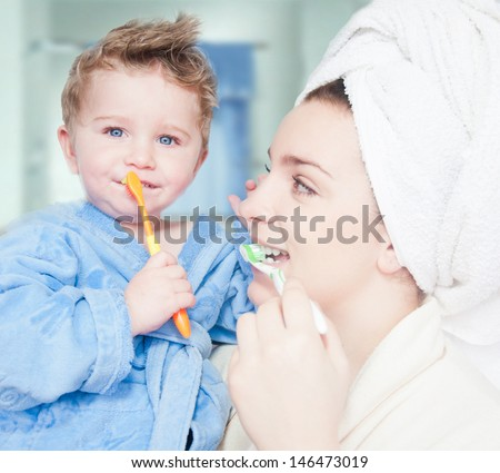 Mother teaches her little son how to brush teeth - stock photo