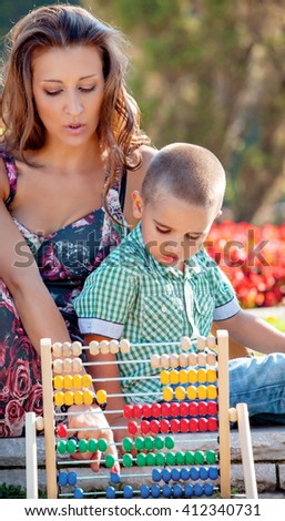 Mother teaches her son mathematics in the summer park on colorful wooden abacus. - stock photo