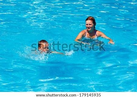 Mother teaches her son to swim in the summer outdoor pool.