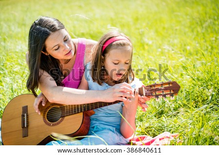 Mother teaches playing guitar her child - outdoor in nature on sunny day