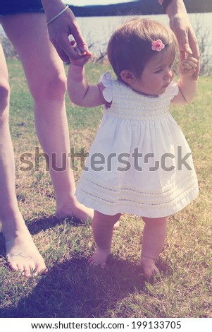 Mother teaching baby girl how to walk - stock photo