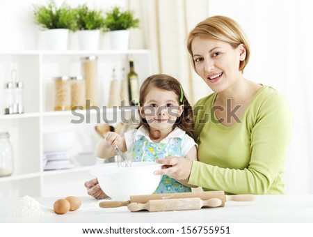 Mother teaching Daughter how to make dough - stock photo