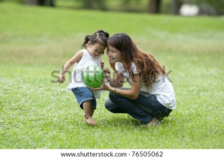 Mother teaching daughter to soccer/ball in the park happily. teen mothers, care, love and warmth closely. Teaching Learning outside the classroom On Mother's Day or Father's Day
