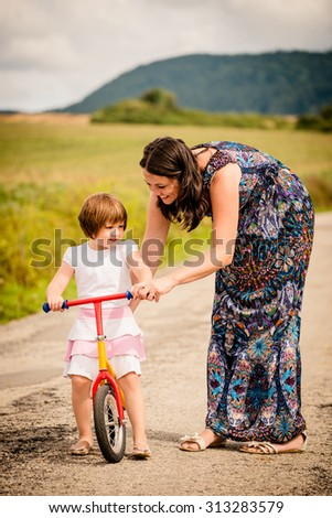 Mother teaching her child riding her firs bike in nature