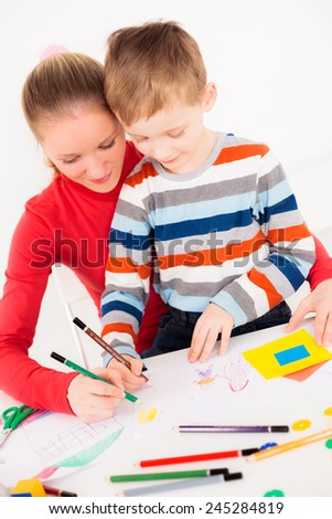 Mother teaching her little boy to draw - stock photo