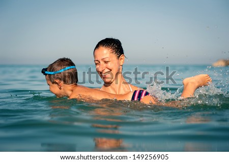 Mother teaching her son how to swim at the sea.