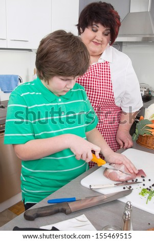 Mother teaching her son to cook meat at kitchen.