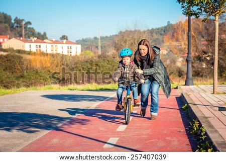 Mother teaching her son to ride a bicycles in the city on a sunny winter day.  Family leisure outdoors concept. - stock photo