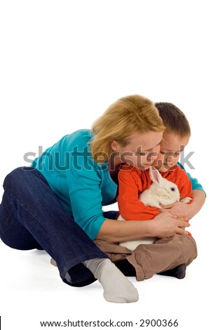 Mother teaching her young child how to hold a bunny (easter theme, isolated) - stock photo