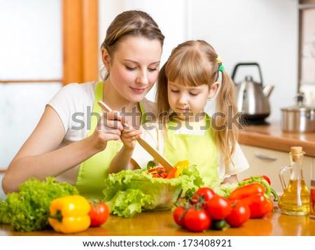 mother teaching kid daughter mixing salad at kitchen - stock photo