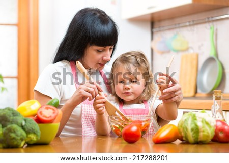mother teaching kid daughter mixing salad at kitchen - stock photo