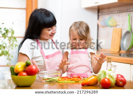 mother teaching kid daughter preparing salad at kitchen - stock photo