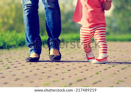 mother teaching little daughter to walk in summer park - stock photo