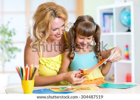 Mother teaching preschooler kid do craft items. DIY concept. - stock photo