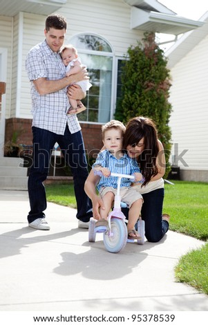 Mother teaching son to ride tricycle while husband holds daughter in background - stock photo