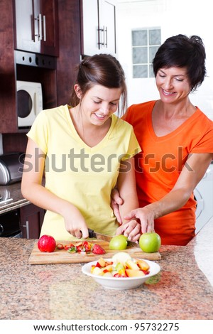 mother teaching teen daughter making fruit salad - stock photo