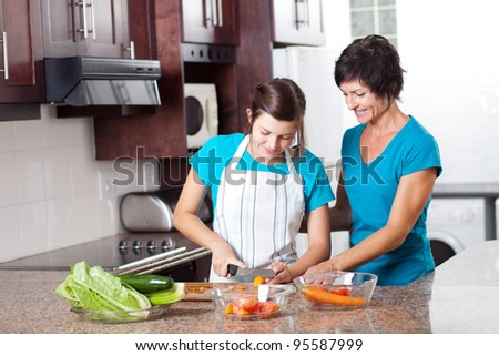 mother teaching teenage daughter cooking in kitchen - stock photo