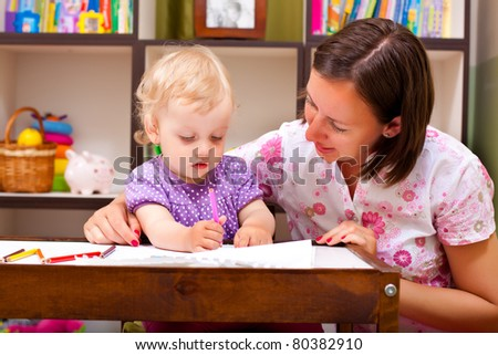 mother teaching to draw hwr daughter - stock photo
