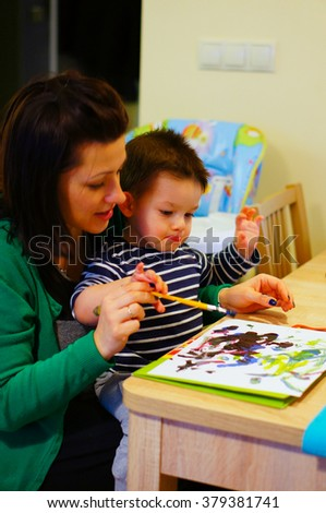 Mother teaching two years old boy how to paint - stock photo
