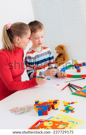 Mother tells her son how to draw - stock photo