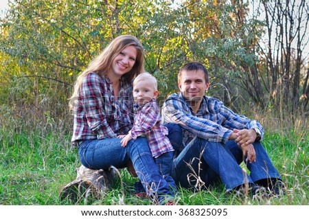 Mother, the father and the son in the autumn wood - stock photo