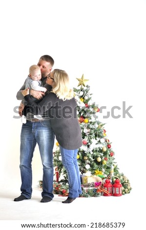 Mother, the father and their small child stand near Christmas tree - stock photo