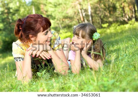 Mother together with the daughter lay on a lawn, smile, look in the face to each other.
