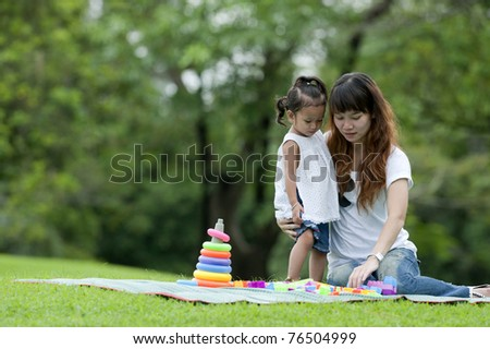 Mother took her daughter to a picnic in the gardens of the Athabasca Becket. Daughter playing with toys, teen mothers closely. On Mother's Day or Father's Day