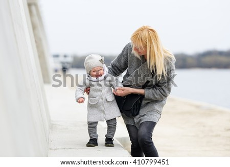 Mother trains the little daughter to go. They are on the river embankment.