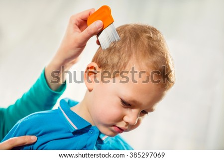 Mother treating son's hair against lice at home - stock photo