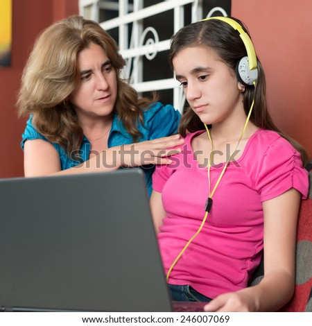 Mother tries to talk to her internet addicted teenage daughter - stock photo