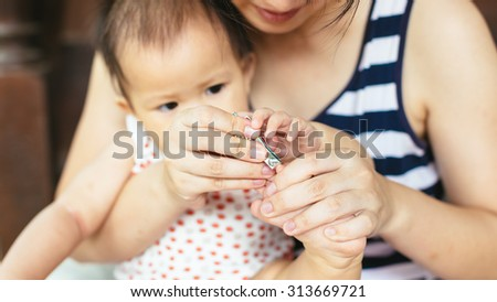 Mother try to nail cutting for her ten months baby. - stock photo
