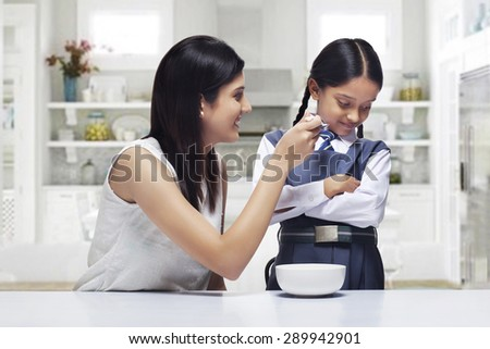 Mother trying to feed daughter breakfast - stock photo