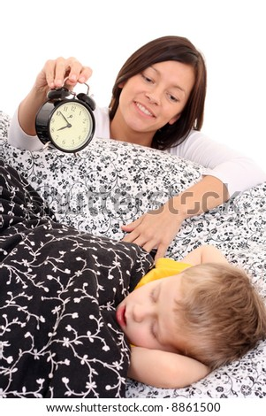 mother trying to wake up 4 years old boy /focus on alarm/